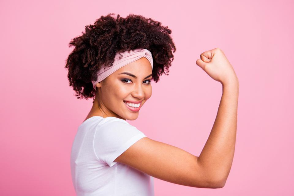 Beautiful young Black and Asian woman flexes bicep against a pink background.