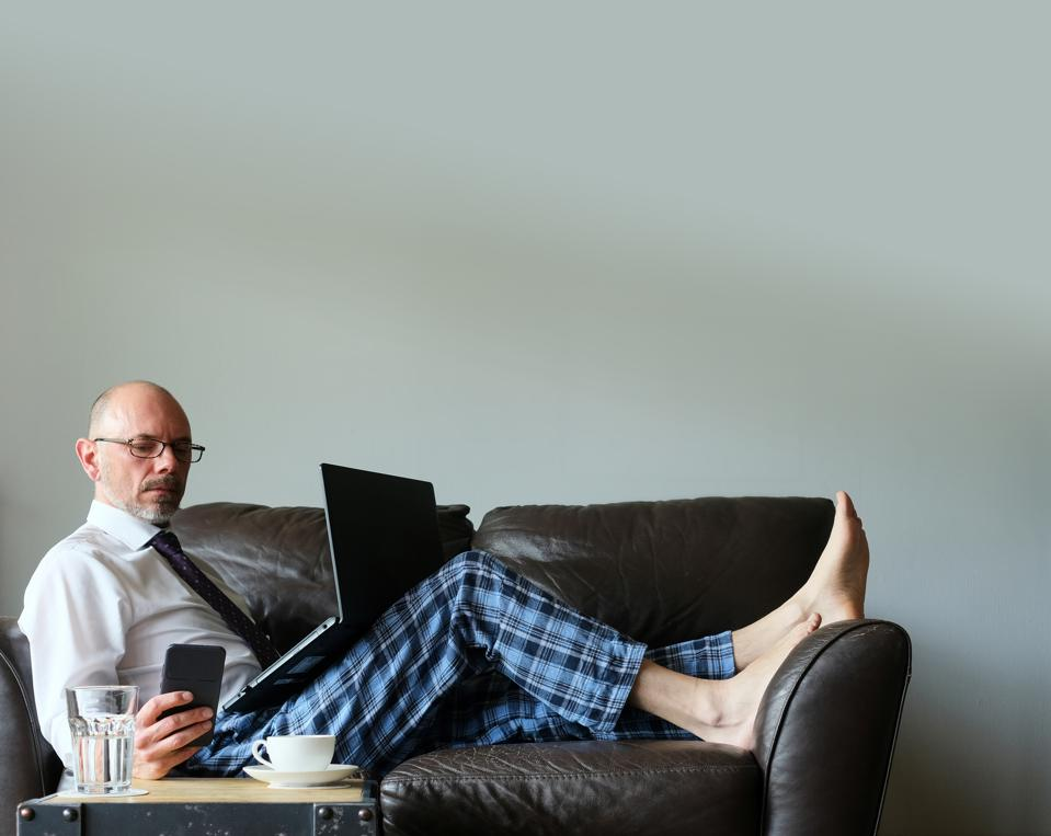 Businessman Working From Home On Couch In Dress Shirt And Pyjama Pants With Laptop And Mobile Smartphone, Stuttgart, Germany