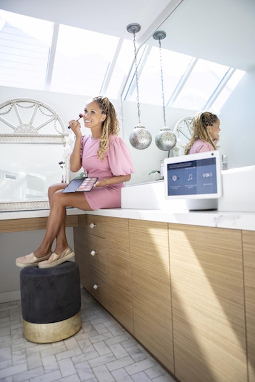 Breegan Jane sits on a bathroom counter applying makeup.