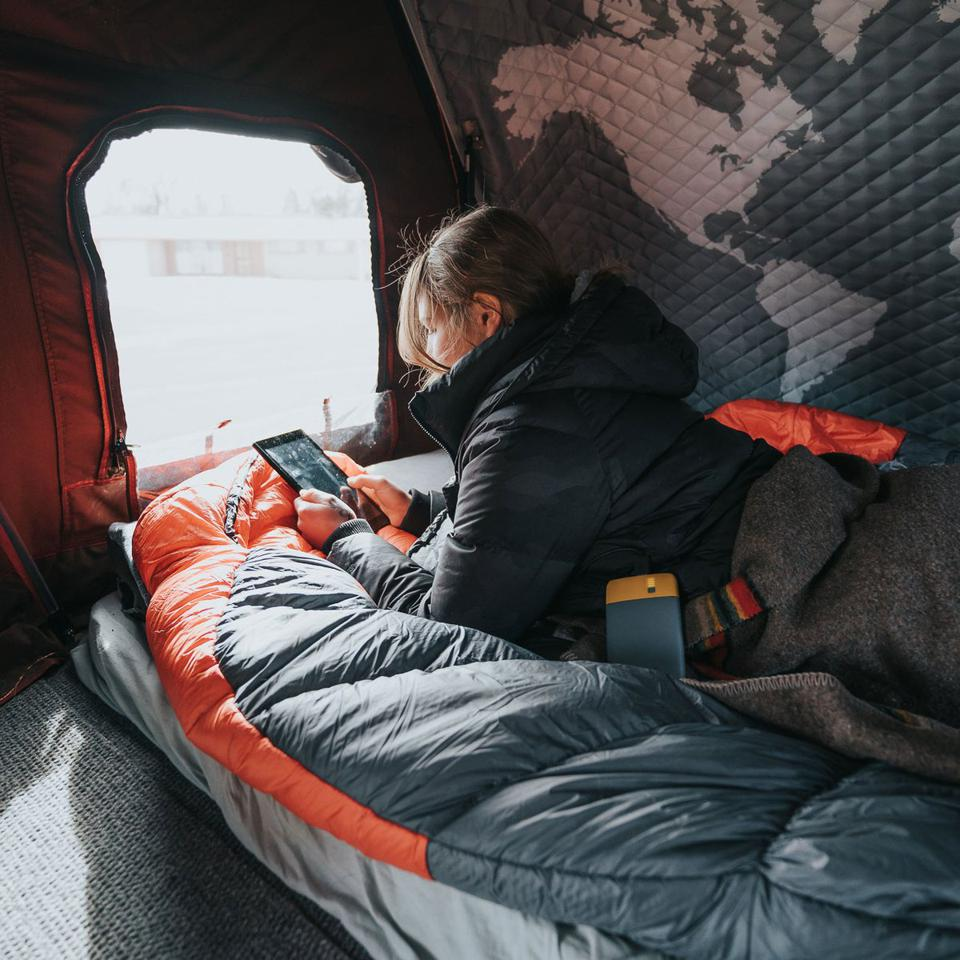 Woman in tent with sleeping bag.