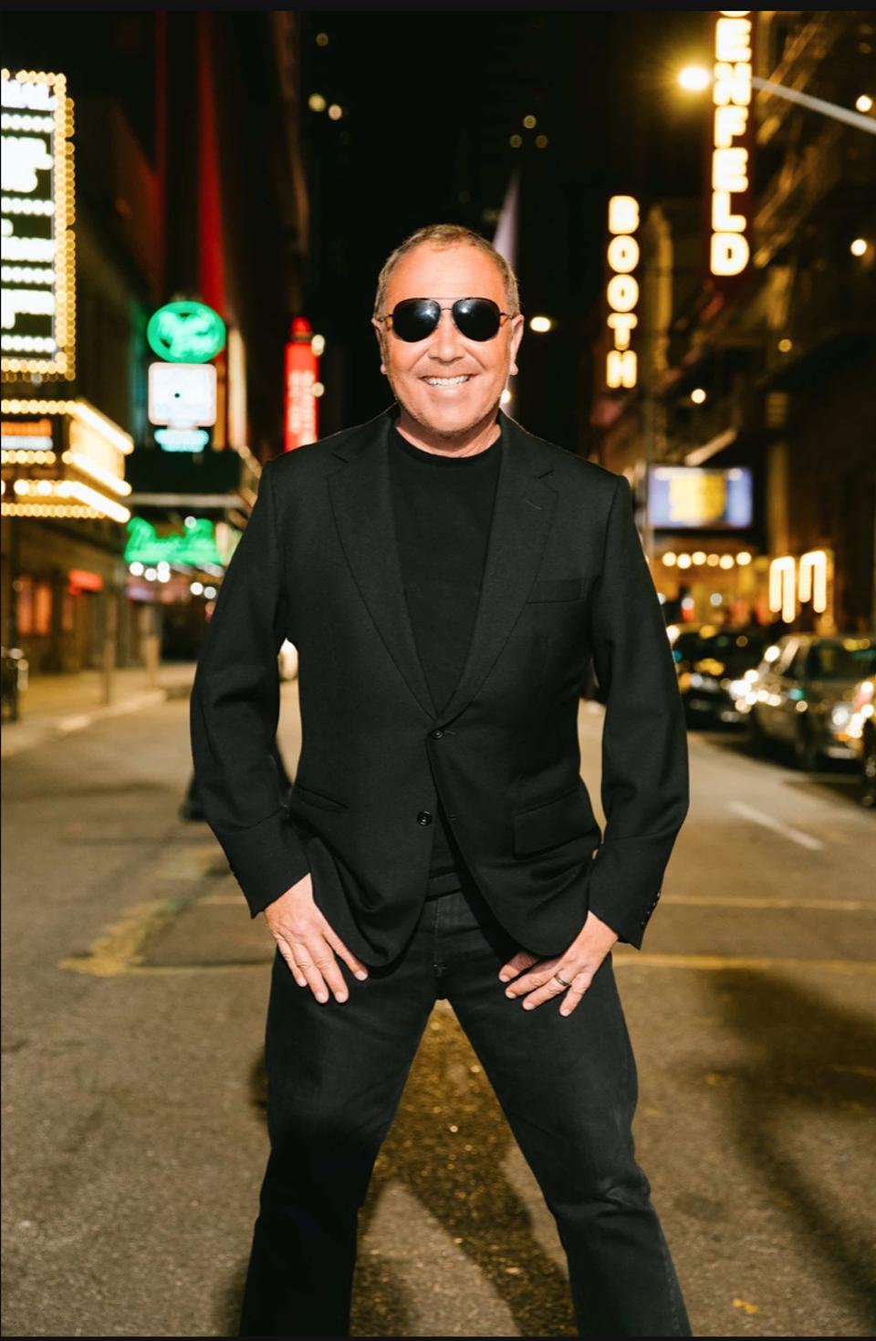 Designer Michael Kors standing on a street near Broadway and Times Square