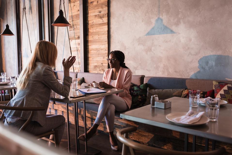 Two business women having coffee break in high-end restaurant