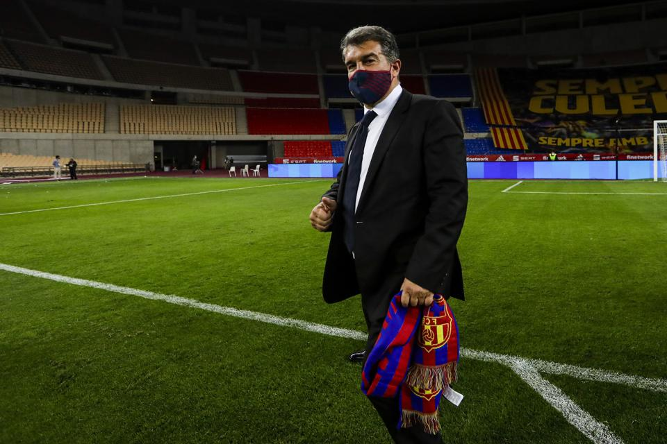 Barcelona president Joan Laporta stands on the pitch with a Barcelona scarf.