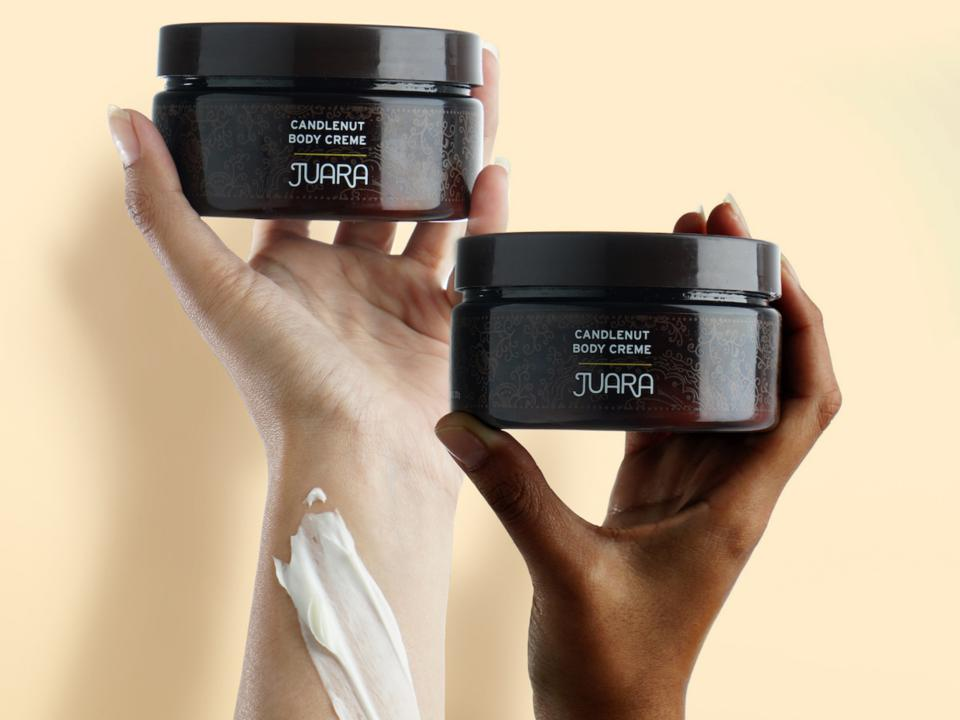 Two hands hold Juara Candlenut Body Creme.