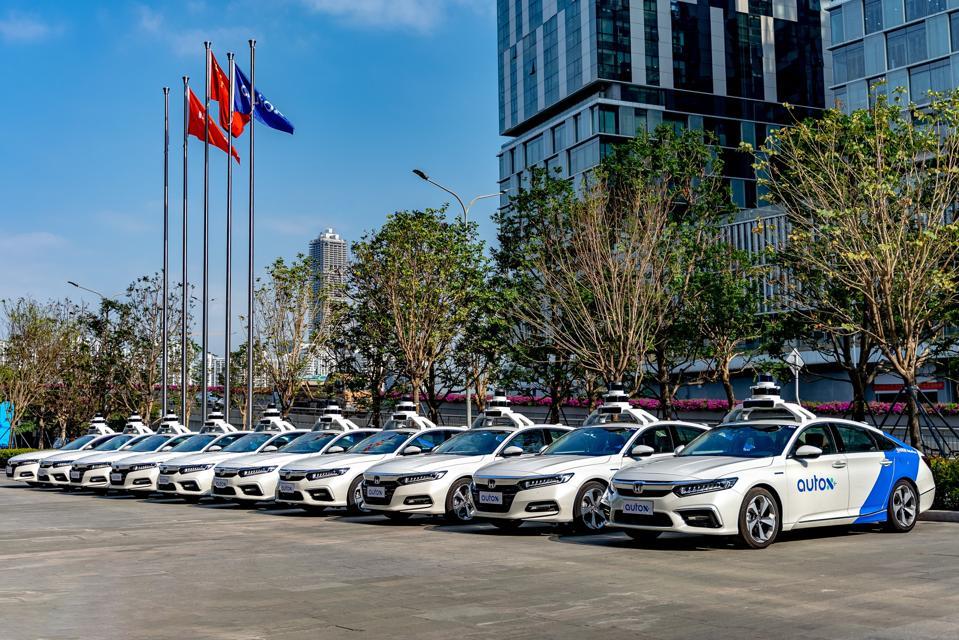 Ten AutoX autonomous Honda sedans parked side-by-side.