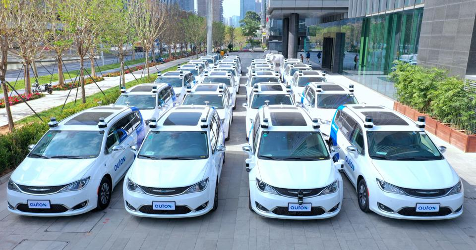 Approximately 25 AutoX minivans on the Chrysler Pacifica platform, parked in Shenzhen.