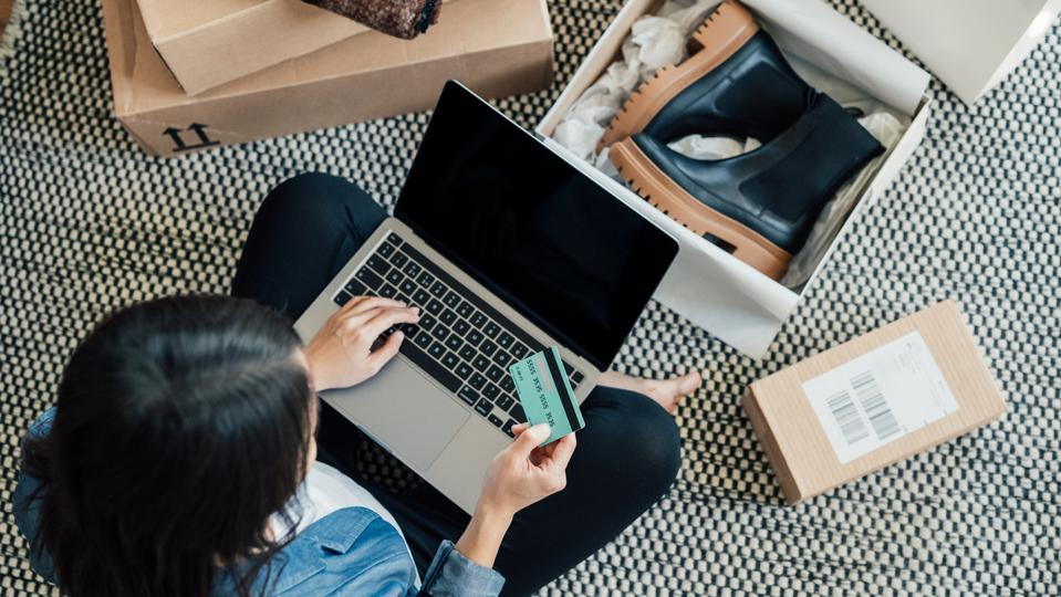 High angle view of a young woman shopping online on laptop, making payment with credit card.