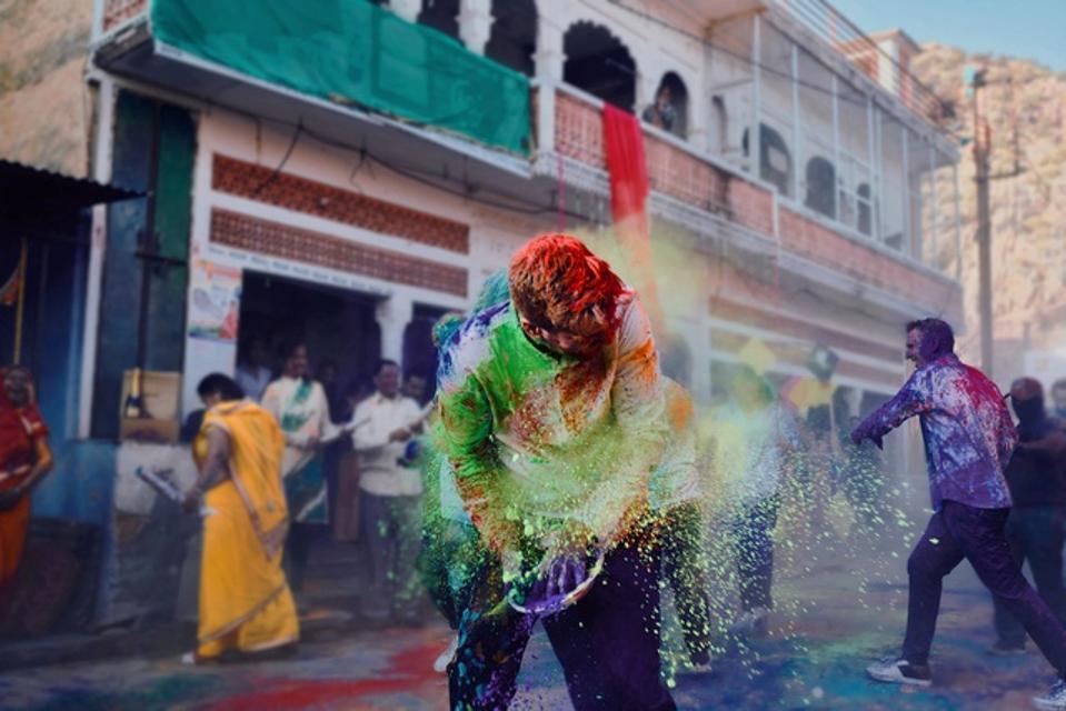 Krug Single Ingredient Trip to India. People laughing throwing colored powder.