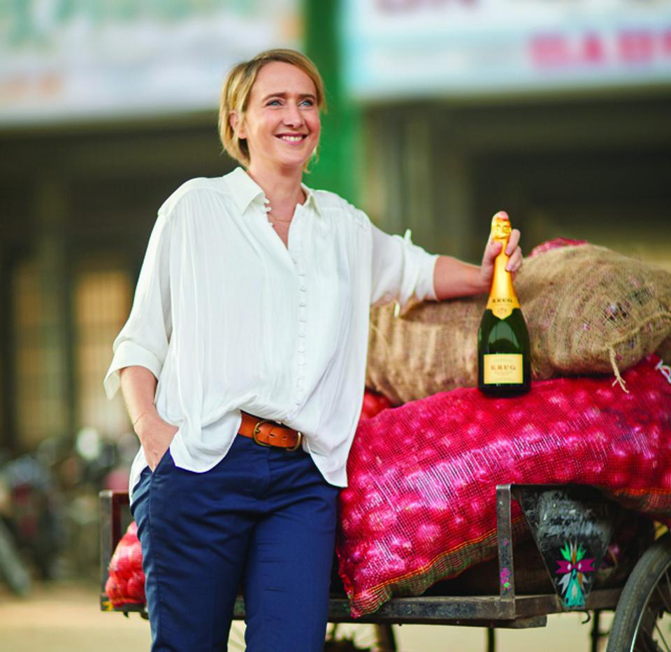 Krug Cellar Master Julie Cavil standing by a cart of onions w/ a bottle of Krug champagne.