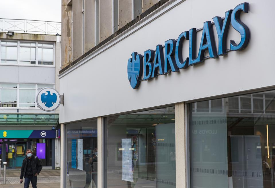 A man walks past Barclays bank logo and branch in Wales. The...