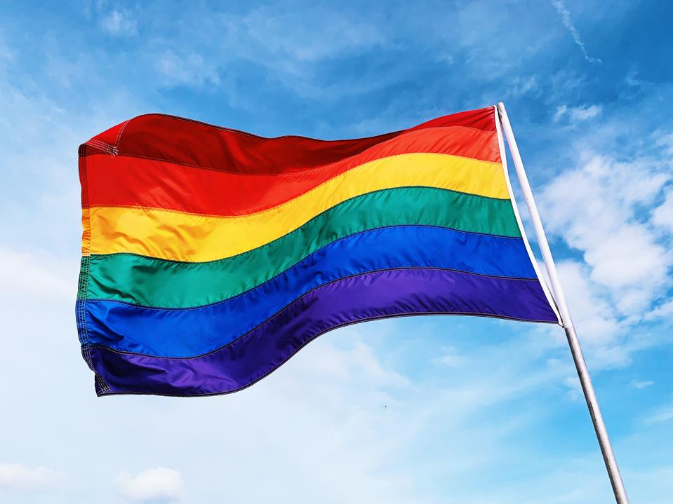 Rainbow flag waving in the wind against blue sky
