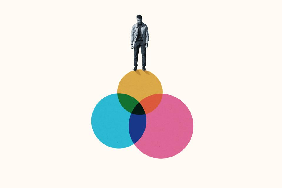 Young man standing on top venn diagram of colorful circles