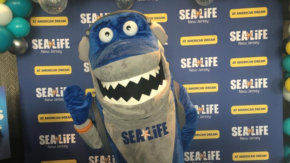 The Sea Life Aquarium mascot in front of a Sea Life sign.