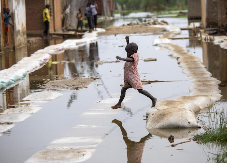 A child crosses floodwaters in Gatumba, a farming community in Burundi that continues to bear the brunt of climate-related shocks.