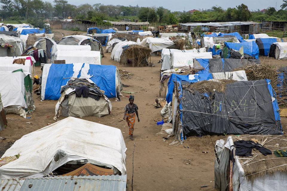 A woman walks through a camp for Burundian families displaced by climate-related disasters.