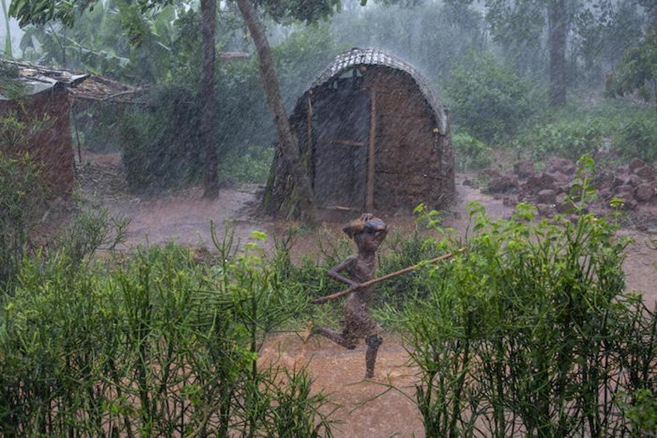 A child runs through a rainstorm in Kibande, northern Burundi.