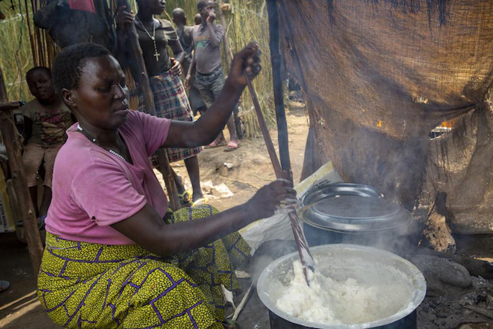 A woman prepares a meal that she will later serve at a restaurant she operates inside a displacement camp in Gatumba, near Bujumbura in Burundi.