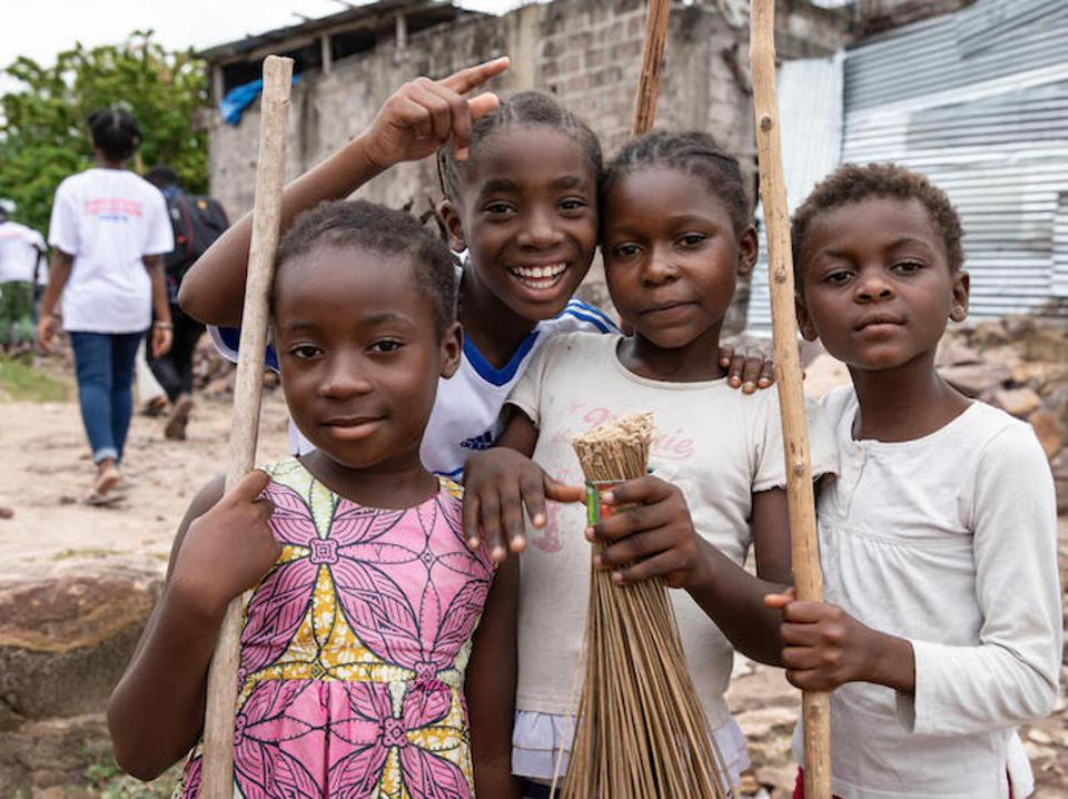 A group of young children from Kinshasa, Democratic Republic of the Congo, pause their clean-up activities to take a photo.