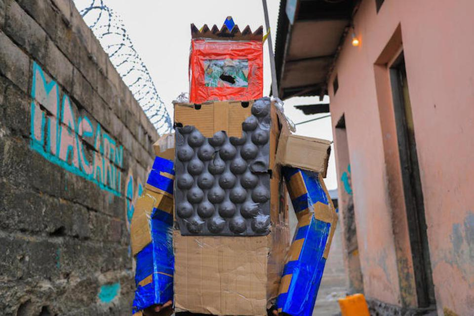 Peggy, 16, models a robot costume she made out of discarded cardboard boxes.