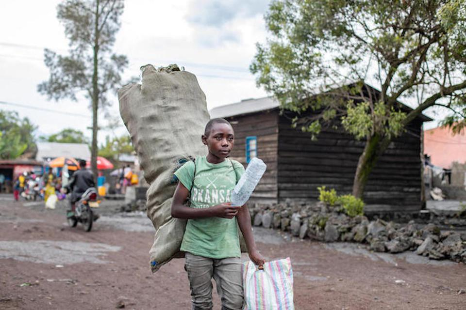 Destin, 15, collects plastic bottles to earn some money and recycle waste.