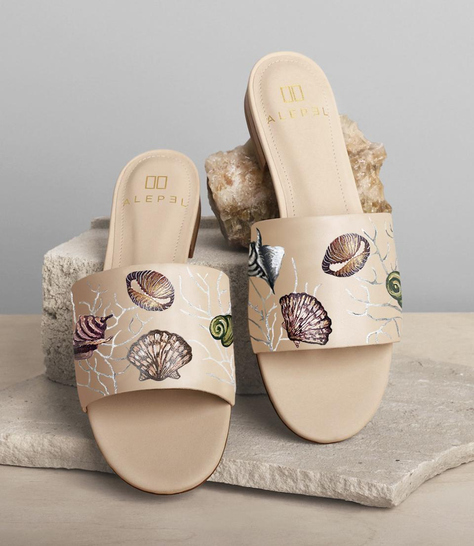 The Alepel x Renna slides feature delicate hand-painted seashells and coral on the genuine leather upper strap.
