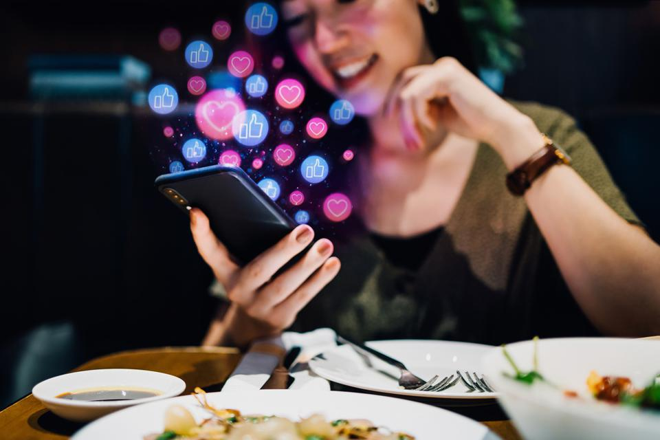 Smiling young Asian woman using smartphone on social media network application while having meal in the restaurant, viewing or giving likes, love, comment, friends and pages. Social media addiction concept