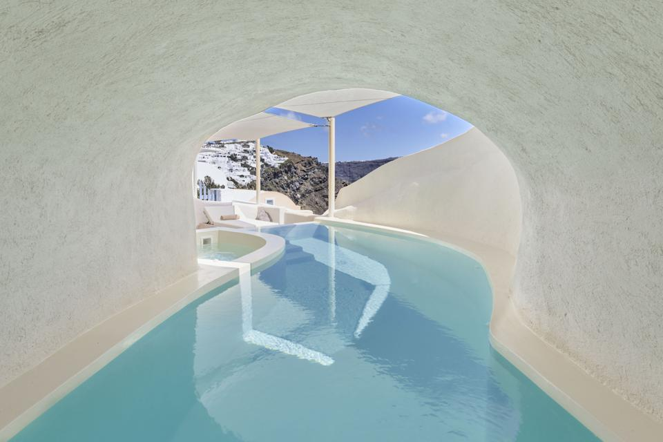 A long swimming pool winds through a tunnel at Mystique resort on Santorini, Greece