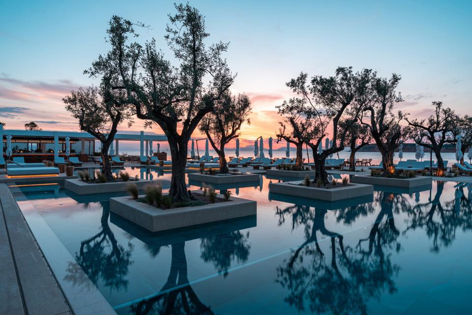rees are reflected in the pool at Four Seasons Astir Palace on the Athens Riviera, Greece