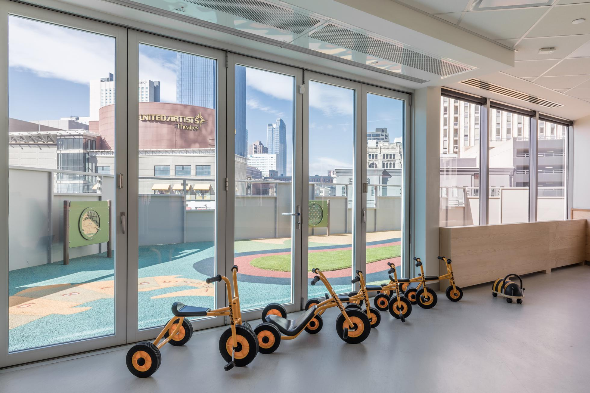 Tricycles of different sizes sit in front of glass doors that lead to an outdoor play area.