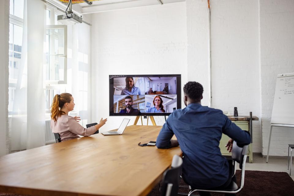 Hybrid work: business men and women in an office, in a meeting with remote colleagues.