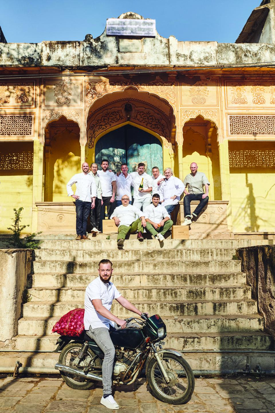 Krug Ambassade Chefs in Jaipur, India standing on stairs with one chef on a motorcycle.