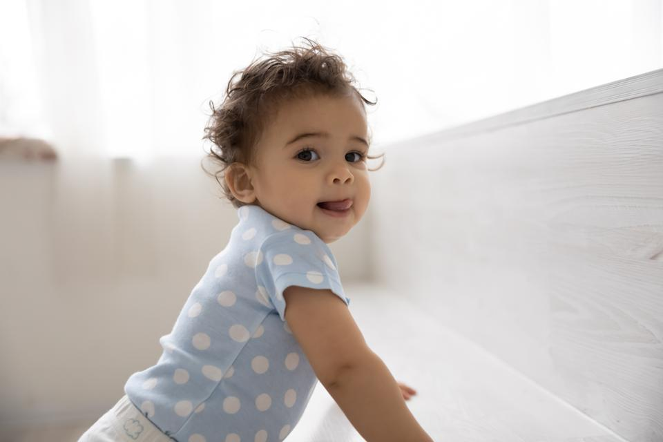 Portrait of cute baby at home, leaning on gray bench