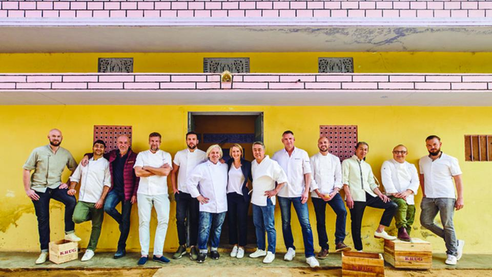 Krug Ambassade Chefs with Julie Cavil standing in front of a yellow wall in Jaipur, India