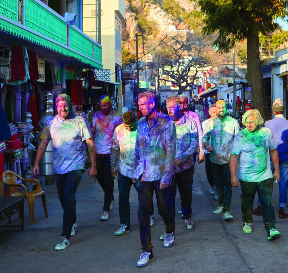 Krug Ambassade Chefs walking in Jaipur, India covered in colorful powder.