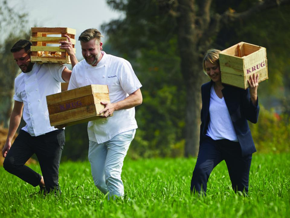 Krug's Cellar Master Julie Cavil & 2 Chefs walking in a field with boxes in Jaipur, India