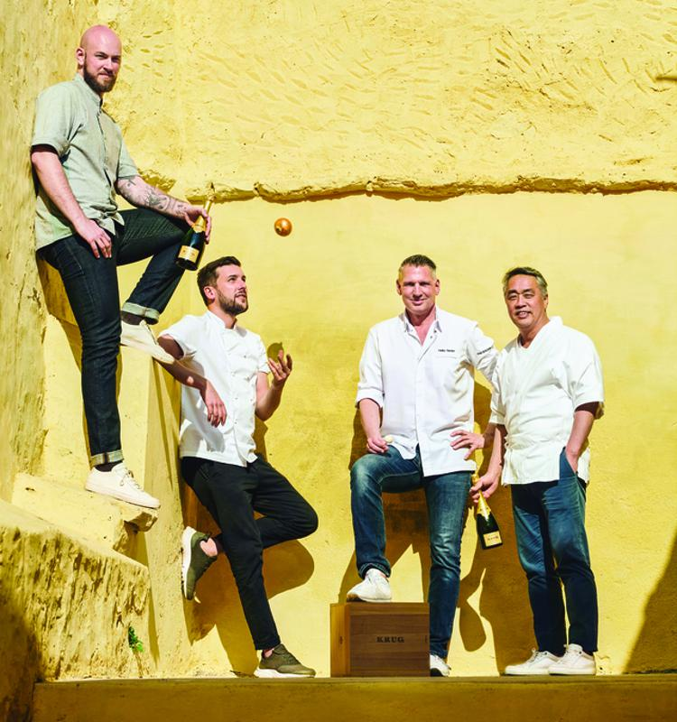 4 Krug Ambassade Chefs standing in front of a yellow wall, 1 is juggling an onion.