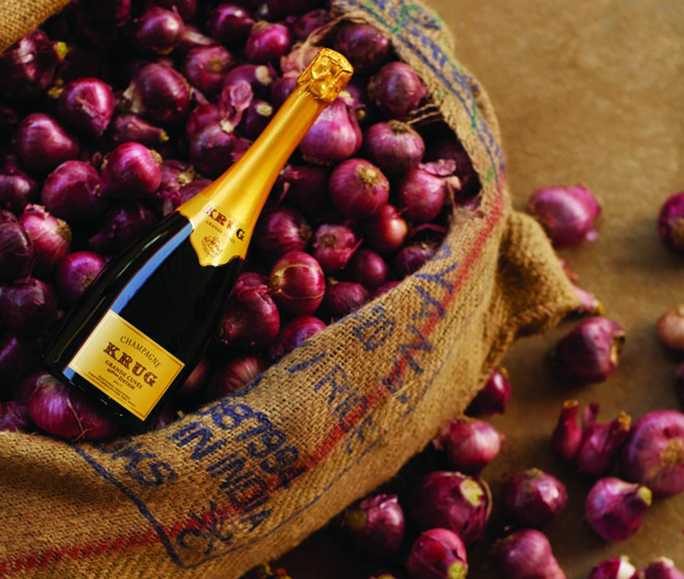 A bottle of Krug resting in a bunch of beautiful onions in a burlap sack.