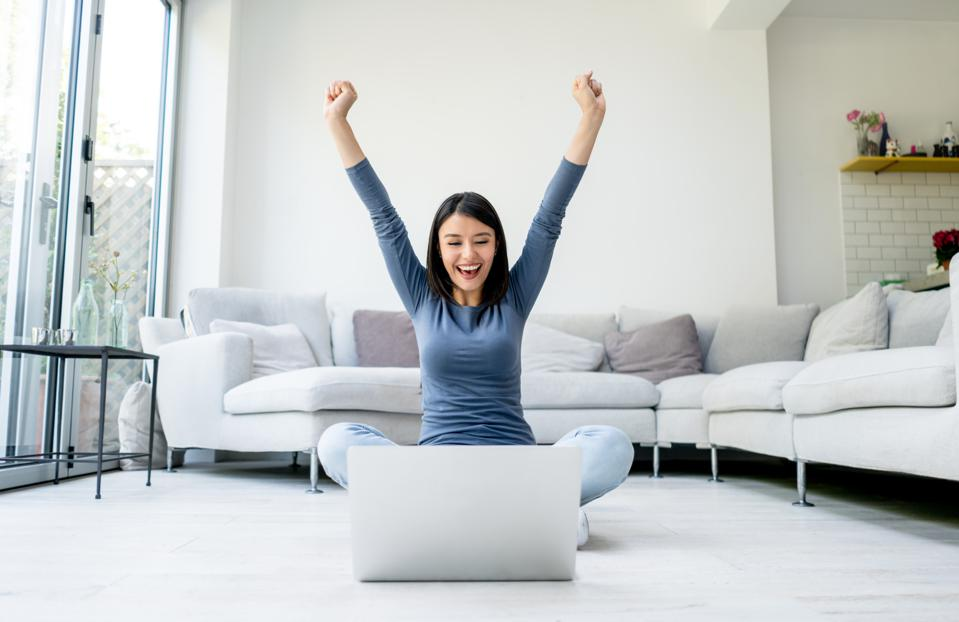Excited woman working on a laptop from home