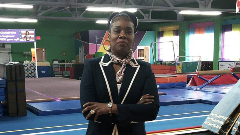 A middle-aged woman wearing a blazer stands in her gym academy.