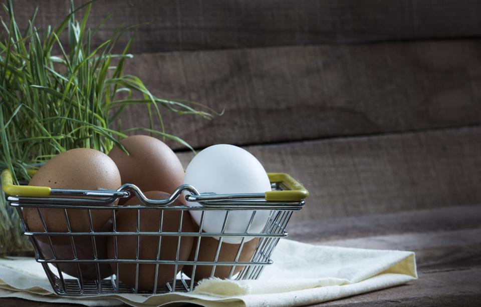 iron food basket with brown and white eggs on a brown wooden background with green grass