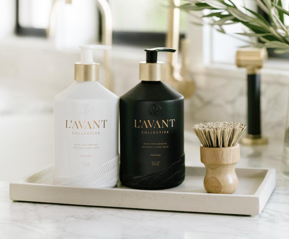 Black and white soap bottles on a tray on kitchen a kitchen sink