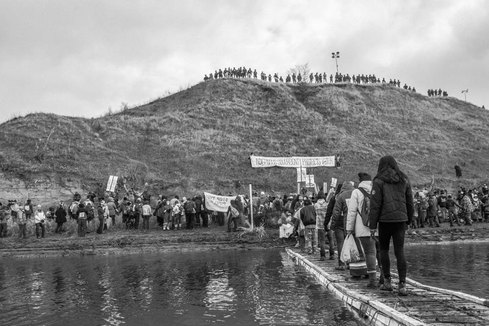 Black-and-white image of protestors crossing a wooden bridge over a river.