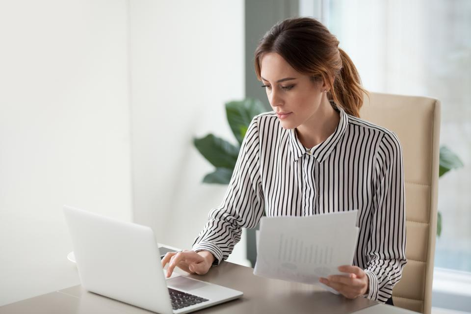 Serious focused businesswoman typing on laptop holding papers preparing report