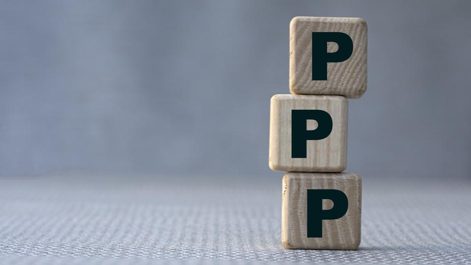 PPP word concept on wooden cubes on gray background