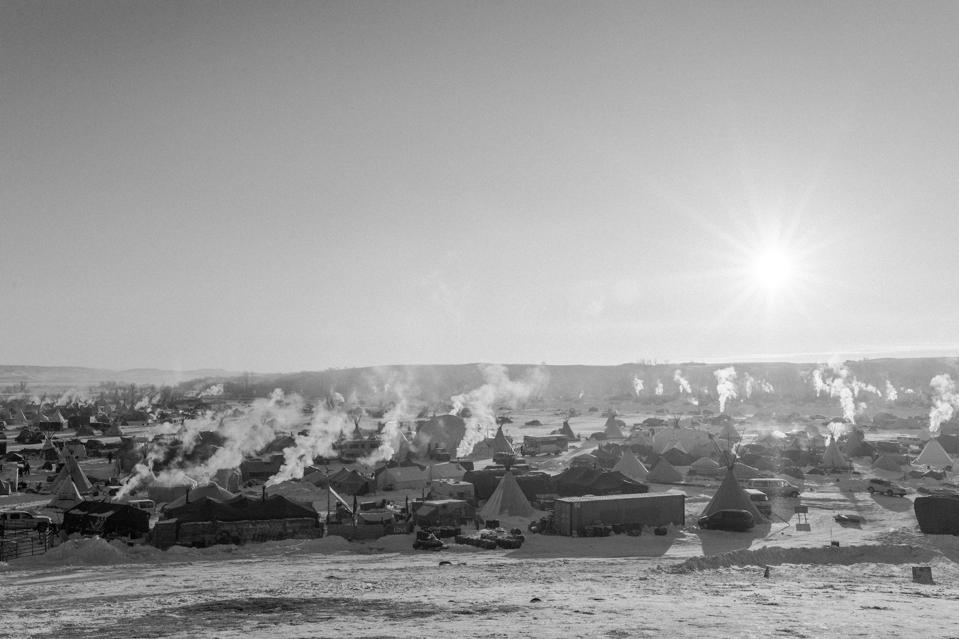 Black-and-white image of a sun rising over a landscape with smoke rising from tipis