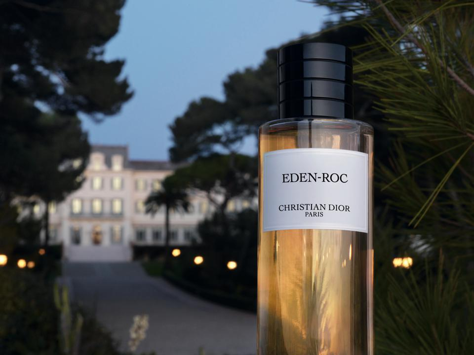 Bottle of perfum with a hotel in the background