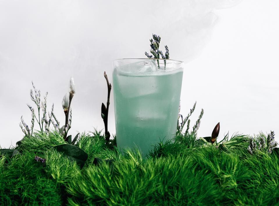 Blue cocktail over a bed of moss and other botanicals