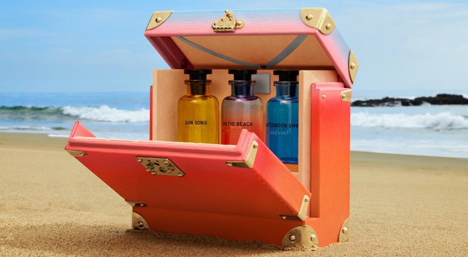 Three Louis Vuitton perfumes in a case, on a beach.