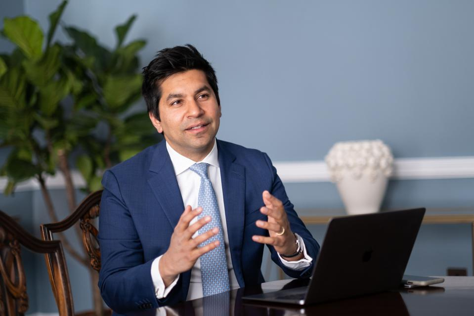 Varun Chandra, Managing Partner, Hakluyt sitting at a table in front of a laptop