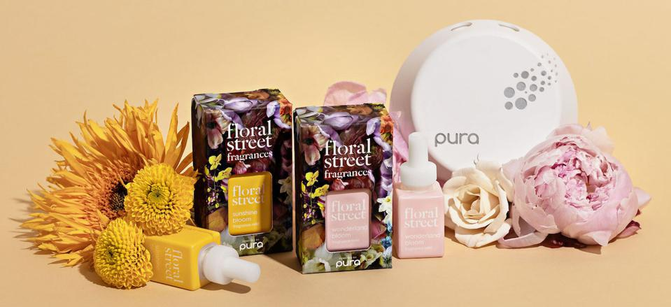 Product shot of Pura Smart Device and Floral Street refills with flowers on a taupe background